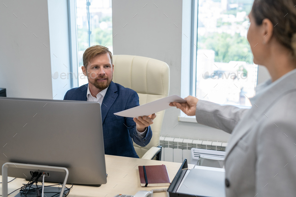 Young businessman taking financial papers given by his colleague - Stock Photo - Images