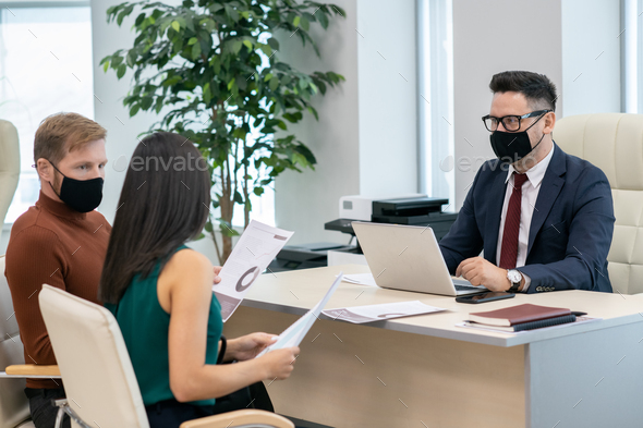 Group of economists in protective masks having discussion - Stock Photo - Images
