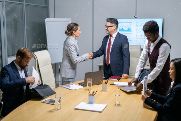 Young businesswoman and mature coach handshaking after seminar or conference - Stock Photo - Images