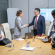 Young businesswoman and mature coach handshaking after seminar or conference - PhotoDune Item for Sale
