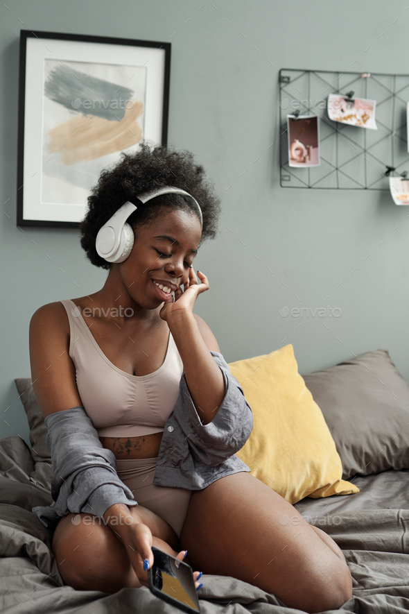 Young smiling woman enjoying music in headphones - Stock Photo - Images