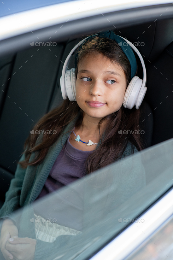 Cute little girl listening to music in headphones while sitting in car - Stock Photo - Images