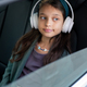 Cute little girl listening to music in headphones while sitting in car - PhotoDune Item for Sale