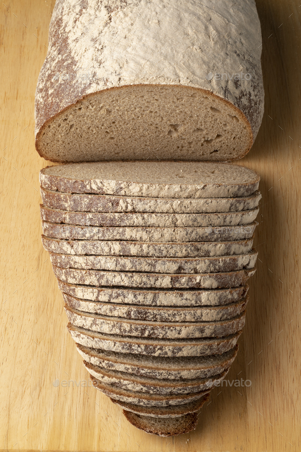 Traditional German sourdough bread and slices on a cutting board - Stock Photo - Images