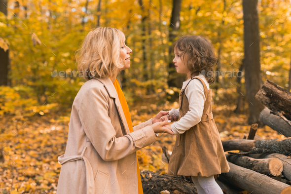 Young mother with her little daughter in an autumn park. Fall season, parenting and children concept - Stock Photo - Images
