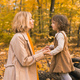 Young mother with her little daughter in an autumn park. Fall season, parenting and children concept - PhotoDune Item for Sale