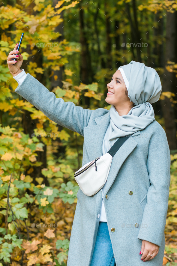 Fashionable young muslim asian girl in hijab taking a selfie on smartphone outdoors in autumn park - Stock Photo - Images