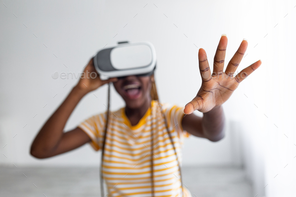 Excited black lady using VR glasses, grabbing something - Stock Photo - Images