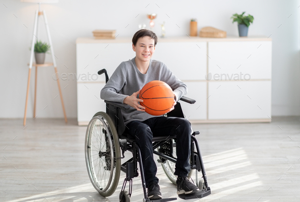 Happy disabled teenage boy holding basketball, sitting in wheelchair and smiling at camera indoors - Stock Photo - Images