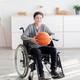Happy disabled teenage boy holding basketball, sitting in wheelchair and smiling at camera indoors - PhotoDune Item for Sale