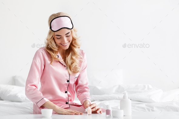 Happy cute caucasian blonde woman in pink pajama with sleep mask put on nail polish - Stock Photo - Images
