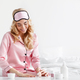 Happy cute caucasian blonde woman in pink pajama with sleep mask put on nail polish - PhotoDune Item for Sale