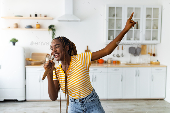 Young black woman having fun while cooking at kitchen - Stock Photo - Images