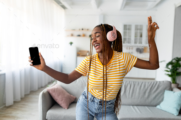 Joyful afro american long-haired woman singing and dancing, using smartphone - Stock Photo - Images