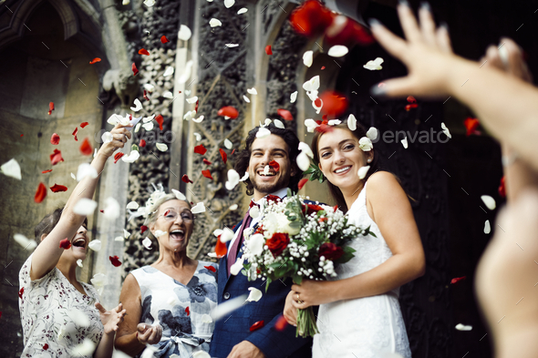 Family throwing rose petals at the newly wed bride and groom - Stock Photo - Images