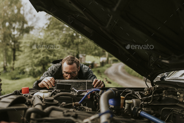 Man repairing a car engine outdoors - Stock Photo - Images