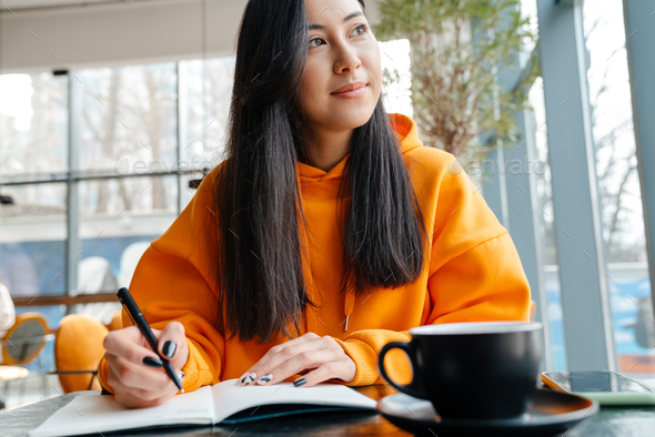 Pleased asian woman writing down notes while sitting in cafe - Stock Photo - Images