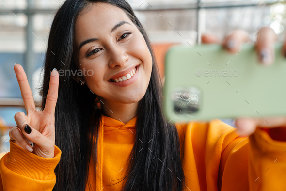 Smiling asian woman gesturing peace sign while taking selfie on cellphone - Stock Photo - Images