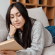 Young happy woman reading book while sitting on sofa - PhotoDune Item for Sale