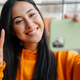 Smiling asian woman gesturing peace sign while taking selfie on cellphone - PhotoDune Item for Sale