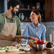 Beautiful young couple is using a digital tablet and smiling while cooking in kitchen at home - PhotoDune Item for Sale
