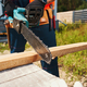 Person sawing off piece of board with chainsaw - PhotoDune Item for Sale