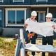 Pair of housebuilders inspecting building layouts outdoor - PhotoDune Item for Sale