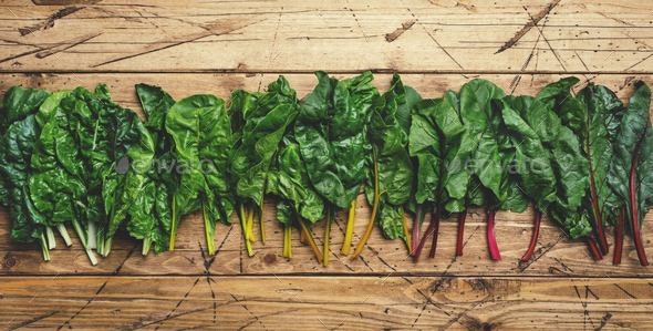 Rainbow swiss chard leaves on wooden background, raw green leaf vegetables, top view, copy space - Stock Photo - Images