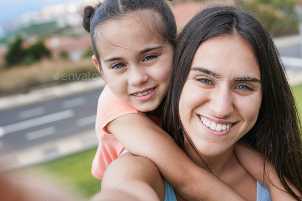 Teenage girl and little cute sister taking a selfie with mobile phone at city park - Stock Photo - Images