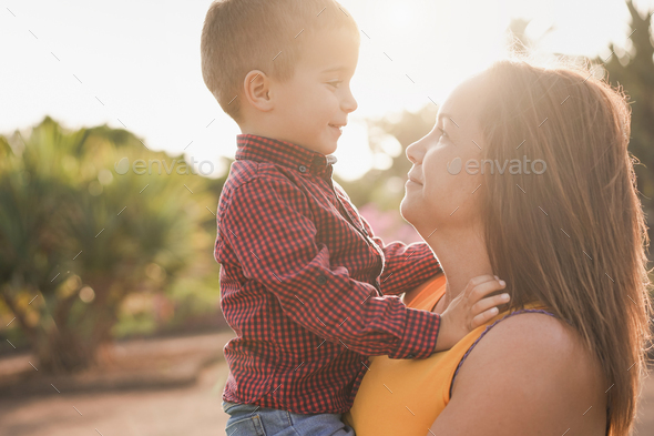 Happy young mother with her son in her arms having tender moment at sunset - Mother and child love - Stock Photo - Images