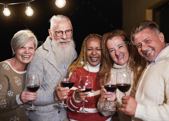 Senior multiracial people smiling on camera while celebrating christmas eve together - Stock Photo - Images