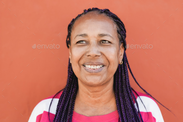 African senior woman smiling with red background - Stock Photo - Images
