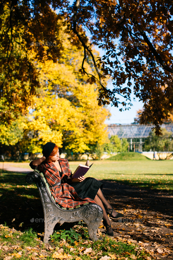 redhead woman in plaid coat and black beret reading book on bench in autumn park at sunny day - Stock Photo - Images