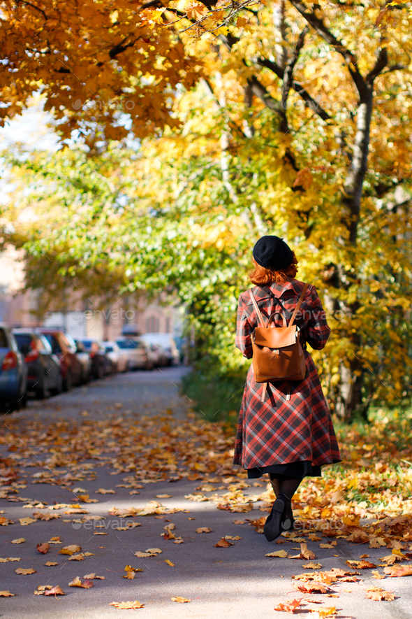redhead woman walking at city street at sunny day. Autumn mood, foliage concept - Stock Photo - Images