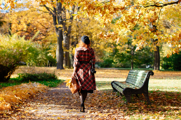 redhead woman in plaid coat and beret walks through the park at sunny day, back view. fall season - Stock Photo - Images