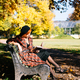 redhead young woman in plaid coat and black beret reading book on bench in autumn park at sunny day - PhotoDune Item for Sale