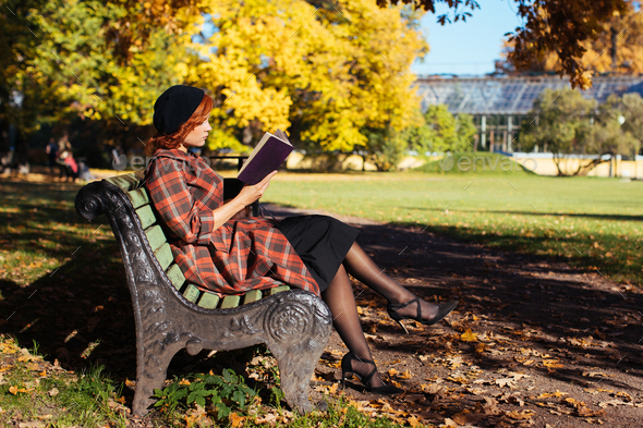 redhead woman reading a book on a bench in autumn park at sunny day. Autumn mood, leisure time - Stock Photo - Images