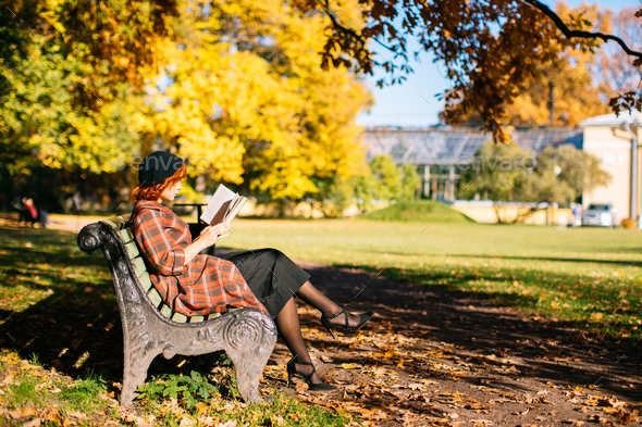redhead girl in checked coat and beret reading book on bench, resting in autumn park at sunny day - Stock Photo - Images