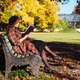 redhead woman reading a book on a bench in autumn park at sunny day. Autumn mood, leisure time - PhotoDune Item for Sale