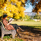 redhead girl in checked coat and beret reading book on bench, resting in autumn park at sunny day - PhotoDune Item for Sale