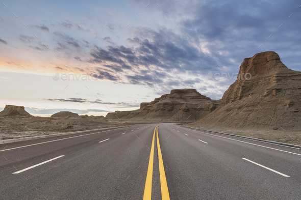 road through the wind erosion physiognomy in sunset - Stock Photo - Images