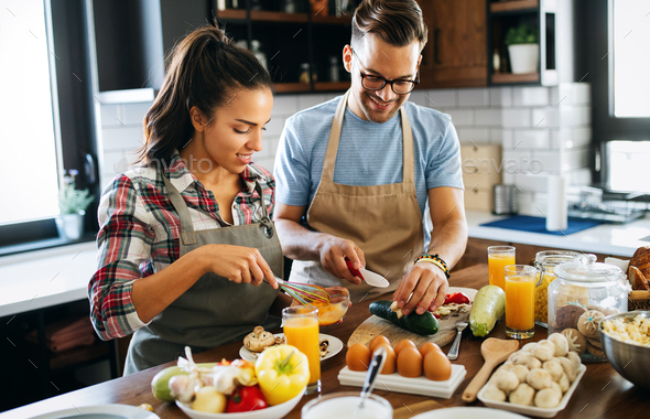 Beautiful couple is smiling while cooking together in the kitchen - Stock Photo - Images