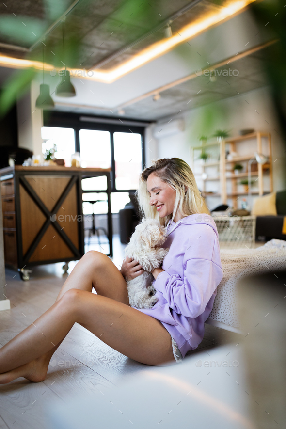 Lifestyle woman with her dog relaxing in living room - Stock Photo - Images