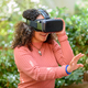 Young woman using a 3D VR headset outdoors on a patio - PhotoDune Item for Sale