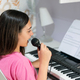 Young girl playing piano and singing at home - PhotoDune Item for Sale