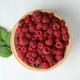 Red juicy raspberries in a wooden bowl on a white wooden background - PhotoDune Item for Sale