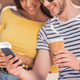 Cheerful young multiethnic couple with coffee cups using smartphone in city - PhotoDune Item for Sale