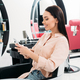 smiling woman sitting at hair salon and looking at smartphone - PhotoDune Item for Sale