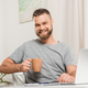 portrait of smiling man with cup of coffee in hand looking at camera - PhotoDune Item for Sale
