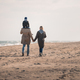 back view of parents with son on shoulders walking on seashore in autumn - PhotoDune Item for Sale
